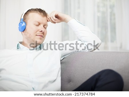 Young man relaxing on a sofa with his feet up listening to music on his earphones with a contented expression and eyes closed in enjoyment - stock photo