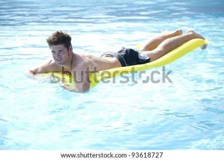 Young man relaxing on air mattress at swimming-pool.