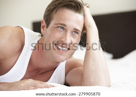 Young Man Relaxing On Bed - stock photo
