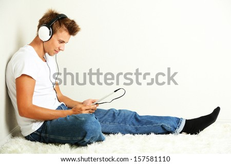 Young man relaxing on carpet and listening to music, on gray wall background - stock photo