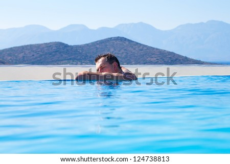 Young Man relaxing on edge of swimming pool  in Greece
