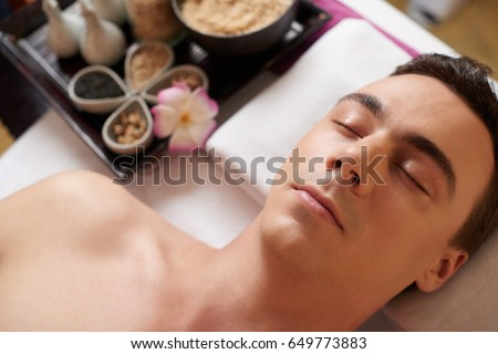 Young man relaxing on massage table after sp procedure