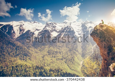 Young Man relaxing on mountain cliff outdoor with mountains on background Lifestyle Travel concept Summer vacations - stock photo