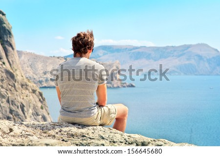 Young Man relaxing on rocky cliff sitting and looking on Sea and mountains Summer time Freedom concept - stock photo