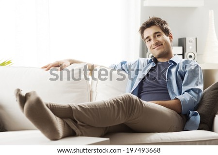 Young man relaxing on sofa in the living room smiling at camera. - stock photo