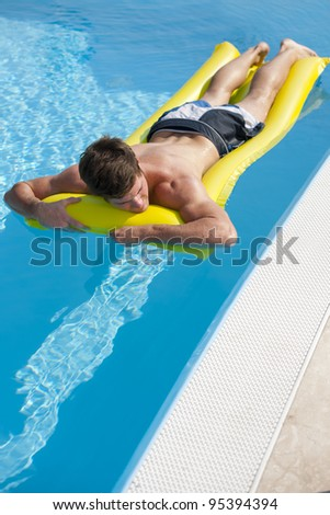 Young man relaxing on swimming-pool - stock photo
