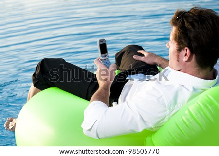 Young man relaxing on the pool, using mobile phone - stock photo