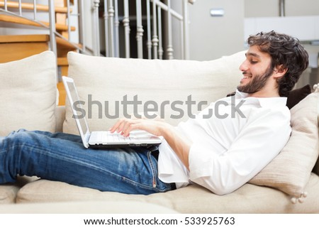Young man relaxing on the sofa with a laptop
