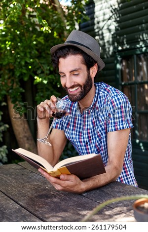 young man relaxing outdoors reading literature novel story book with glass red wine at home - stock photo