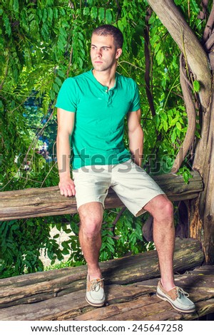 Young man relaxing outside. Wearing a green short sleeve Henley shirt, light yellow shorts, leather casual shoes, a young handsome guy is sitting on tree trunk in woods in hot summer. - stock photo
