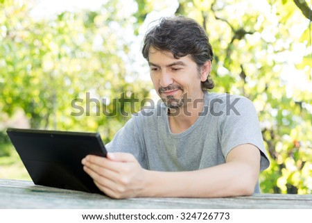 Young man relaxing with a tablet computer at a garden