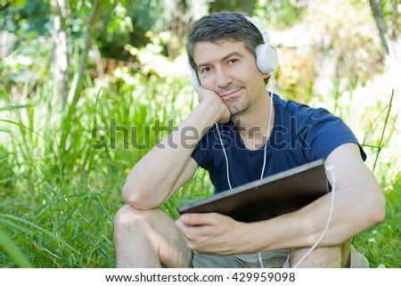 young man relaxing with a tablet pc listening music with headphones on a the park, outdoor - stock photo