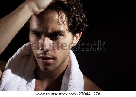 Young man relaxing with towel, black background