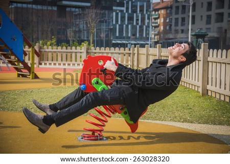 Young man reliving his childhood plying in a children's playground riding on a colorful red spring seat with a happy smile in an urban park - stock photo