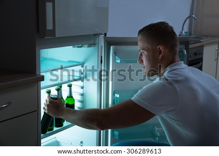 Young Man Removing Beer Bottle From Refrigerator At Night In Kitchen Room