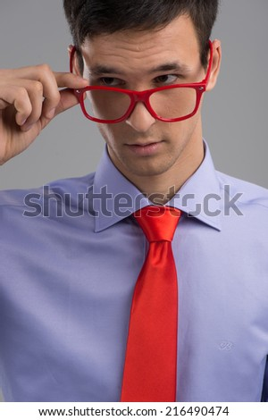 young man removing glasses on grey background. handsome guy wearing red necktie - stock photo