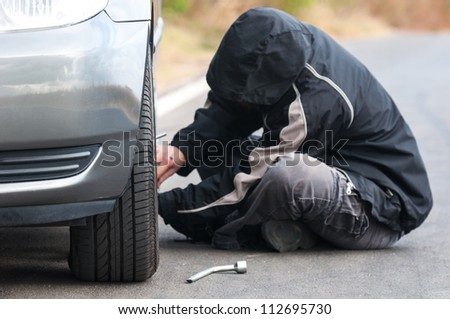Young man repairing car outdoors sitting
