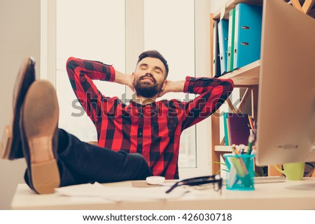 Young man resting after working day and holding legs on table - stock photo