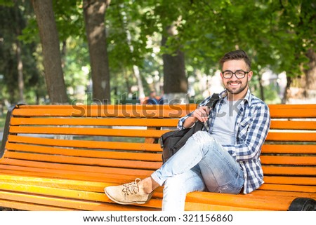 Young man resting on the bench after his hard working day. Smiling man sitting with a bag outdoors in the park and looking at the camera. - stock photo