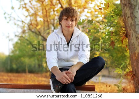Young man resting on the bench in park, outside - stock photo