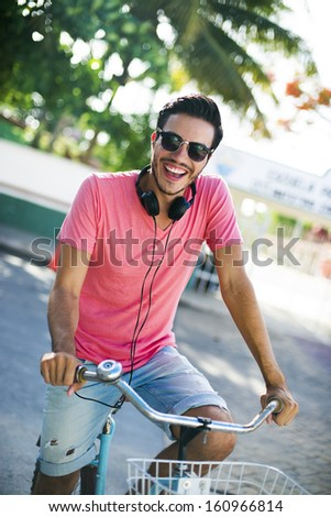 Young man riding a bike across the city with headphones