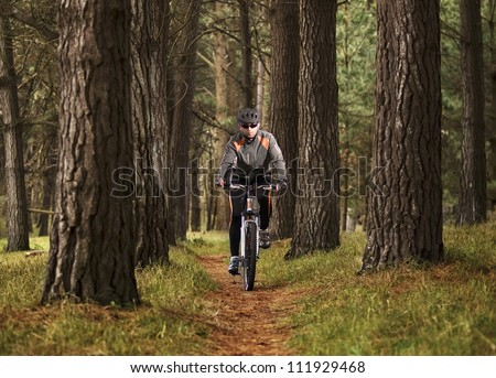 Young man riding a bike through a forest - stock photo