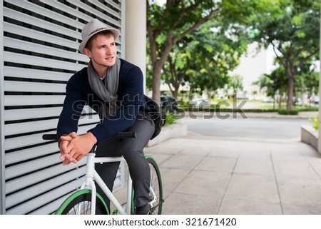 Young man riding fixed gear bike along the street