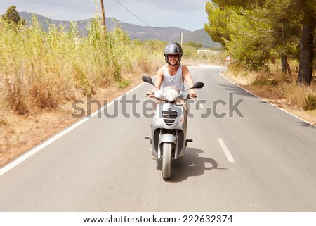 Young Man Riding Motor Scooter Along Country Road - stock photo