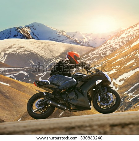 young man riding motorcycle on asphalt country road with sun shining and mountain background use for sport activities,male leisure and journey theme - stock photo