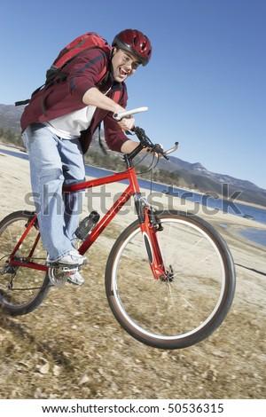 Young Man riding mountain bike on lake shore - stock photo