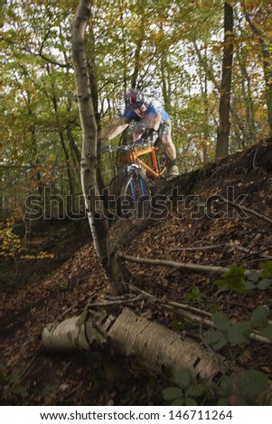 Young man riding mountain bike through forest