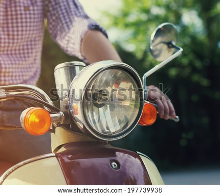 Young man riding old retro scooter in a city street - stock photo