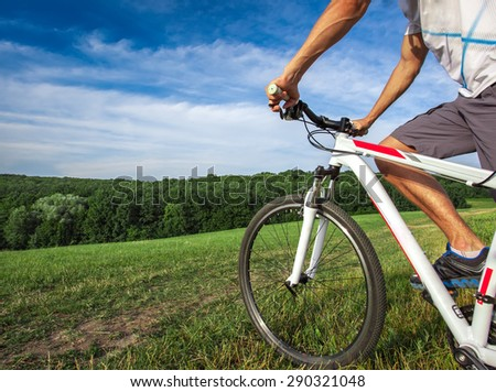 Young man riding on a bicycle on green meadow with a backpack - stock photo