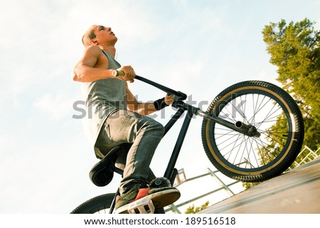 Young man riding on a BMX bicycle on a ramp over blue sky background  - stock photo