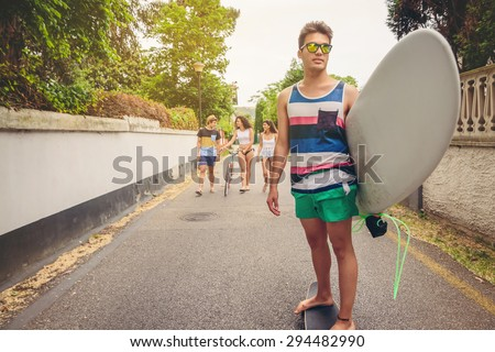 Young man riding on a skate and holding surfboard with group of friends having fun in the background on a sunny day. Summer lifestyle concept. - stock photo