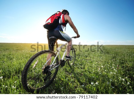 Young man riding on bicycle through deep grass with red backpack - stock photo