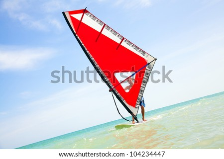 young man riding  red windsurfing sail on the sea