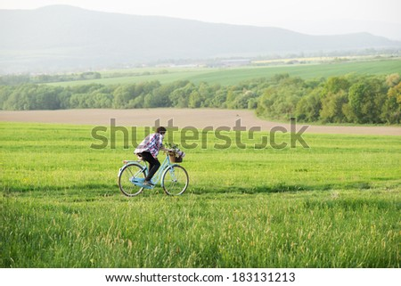 Young man riding vintage bike on the green meadow