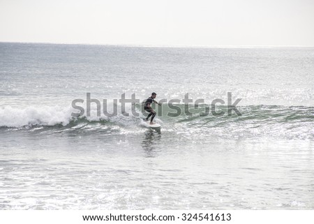 Young man riding wave at sunset