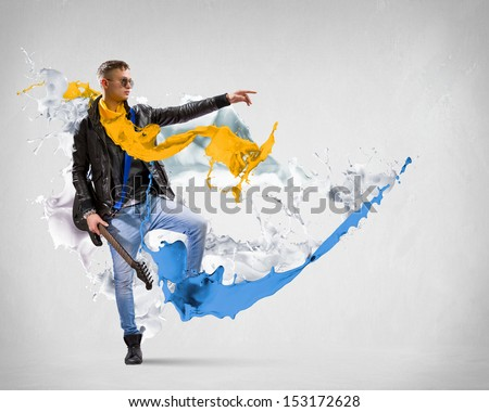 Young man, rock musician in jacket playing guitar