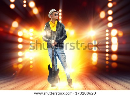 Young man, rock musician in jacket with guitar - stock photo