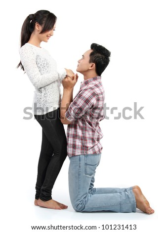 Young man romantically proposing to girlfriend isolated on white background