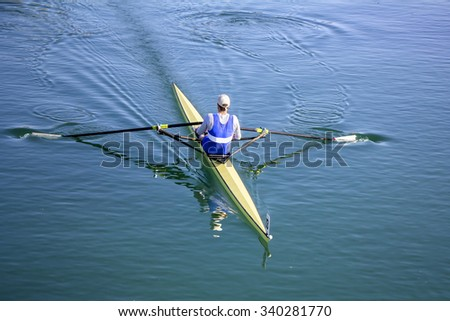 Young man Rower in a boat, rowing on the tranquil lake - stock photo