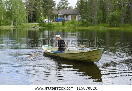 Young man rowing a boat on a lake - stock photo
