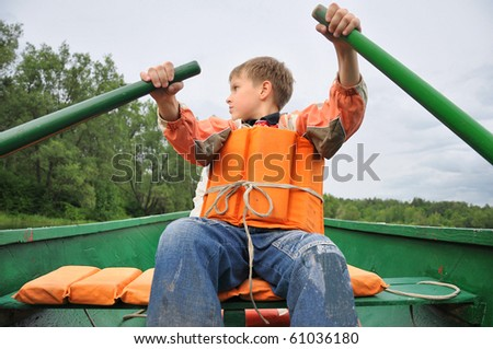 Young man rowing a boat on the river. - stock photo