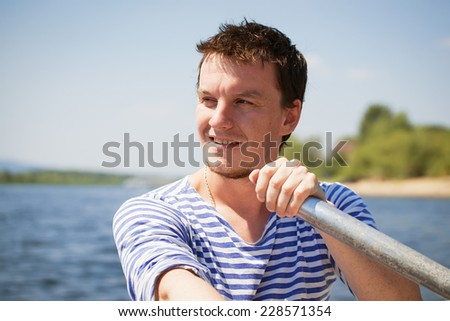 young man rows the boat - stock photo