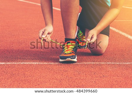 Young Man Runner tying his shoes on a running track. Shoelaces, Urban jogger