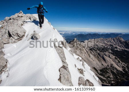 Young man running along snowy mountain ridge - stock photo