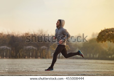 Young man running at park during winter, autumn morning