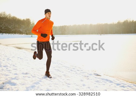 Young man running at winter in park - stock photo